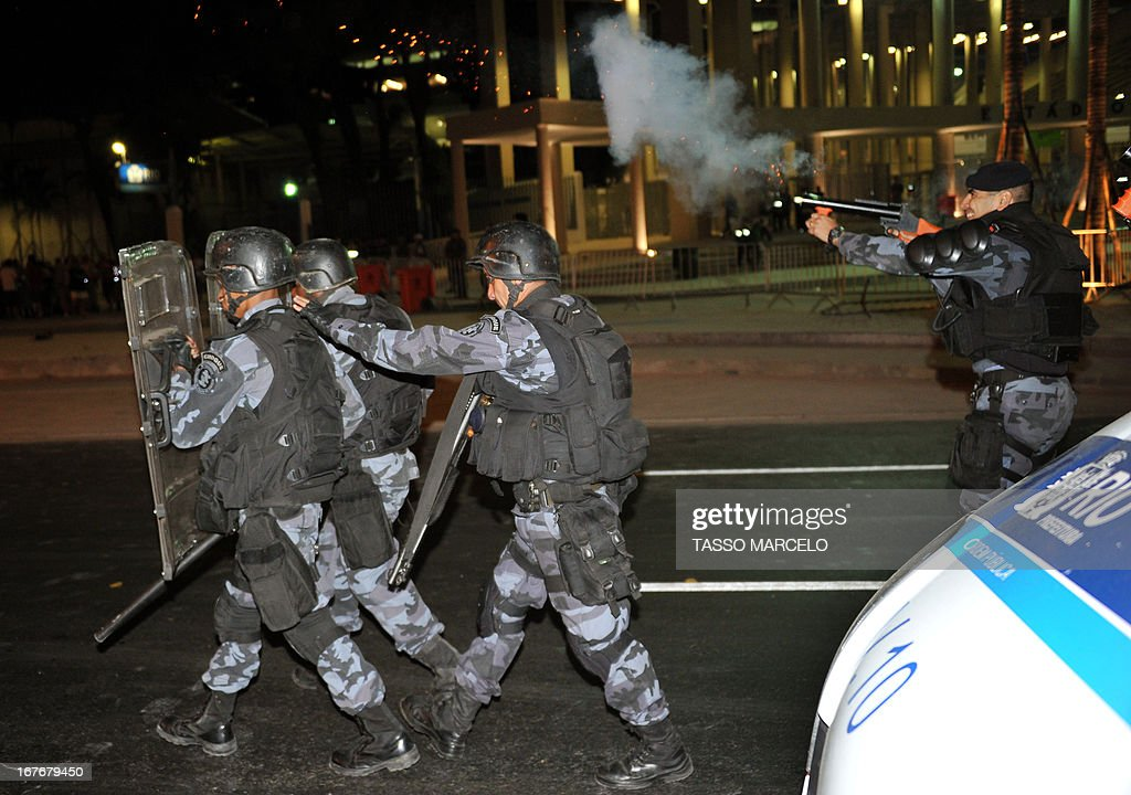 Riot policemen take their positions outside the Mario Filho --Maracana-- stadium during a protest against Maracana's privatization and the demolition of the former Indigenous Museum, at the time that a test event is taking place in the Maracana stadium, in Rio de Janeiro on April 27, 2013. The Maracana will host the upcomig Confederations Cup --next June--, the Brazil 2014 FIFA World Cup and the 2016 Summer Olympics.