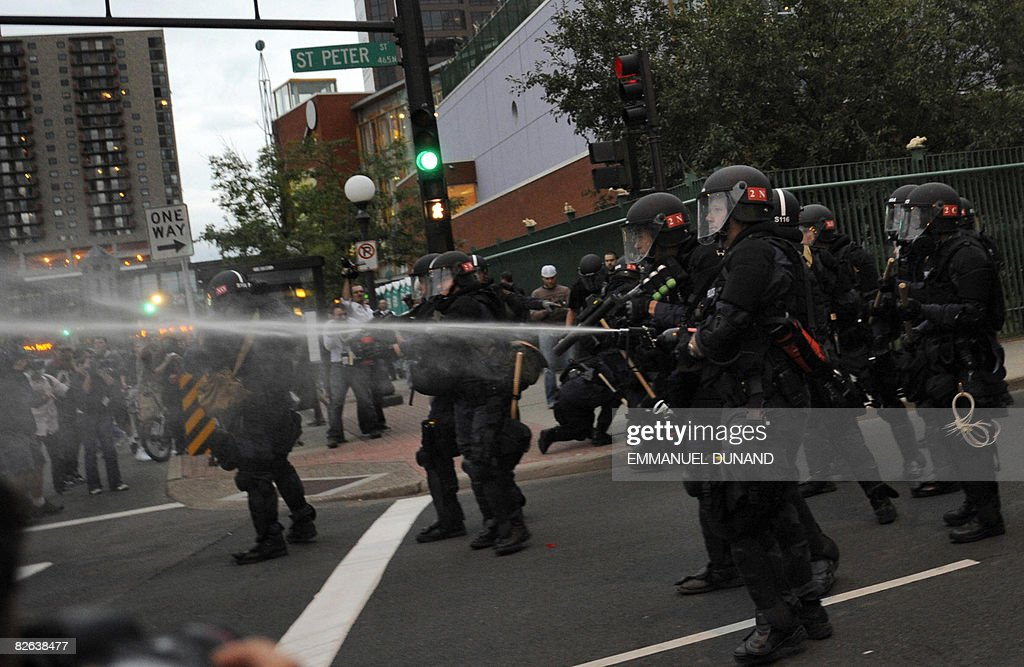 Riot policemen use pepper spray during a clash with antiwar and antipoverty protesters near the Republican National Convention being held at the Xcel...