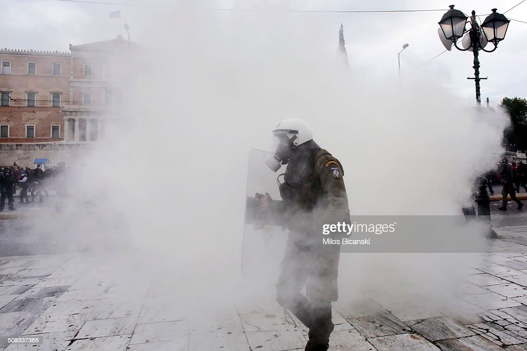 Riot policemen use tear gas during a 24-hour nationwide general strike on February 4, 2016 in Athens, Greece. Clashes have broken out between Greek police and youths throwing fire bombs and stones, as tens of thousands of people march through central Athens to protest planned pension reforms.