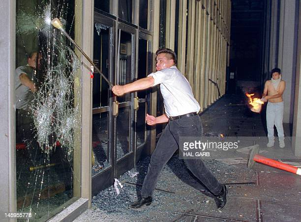 A rioter breaks a glass door of the Criminal Courts building downtown Los Angeles 29 April 1992 after a jury acquitted four police officers accused...