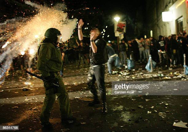 Rioters and a policeman stand near a fire started during May Day clashes in Kreuzberg on May 1 2009 in Berlin Germany Berlin police earler in the day...