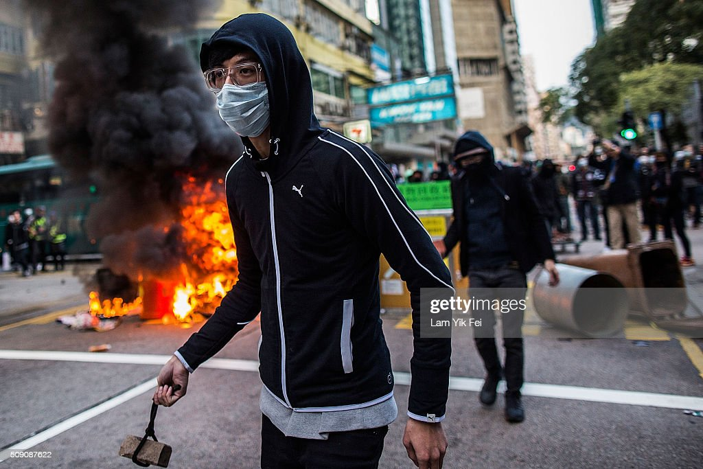 Rioters throw bricks at police in Mong Kok district of Hong Kong on February 9, 2016 in Hong Kong. More than 40 police officers and journalists have been injured after a riot with protesters on the first day of Chinese New Year celebrations.