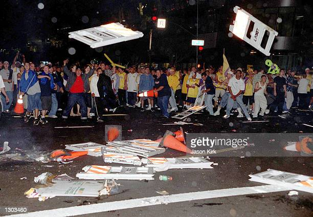 Rioting fans throw police barricades into the streets June 19 2000 in Los Angeles CA following the Los Angeles Lakers'' victory in the NBA Finals...
