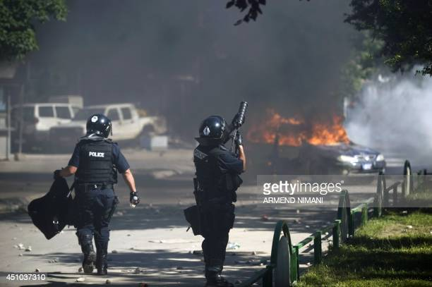 A riotpolice officer fires a tear gas grenade during clashes with protesters on June 22 2014 in the divided town of Mitrovica Kosovo police used tear...