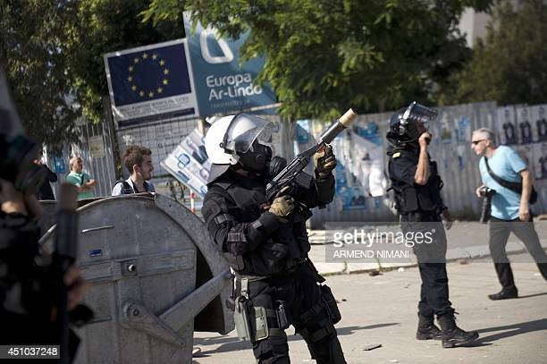 A riotpolice officer prepares to fire a tear gas grenade during clashes with protesters on June 22 2014 in the divided town of Mitrovica Kosovo...
