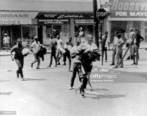 Riots in the Watts section with Negro youths carrying armloads of clothes running from looted stores Los Angeles California August 1965