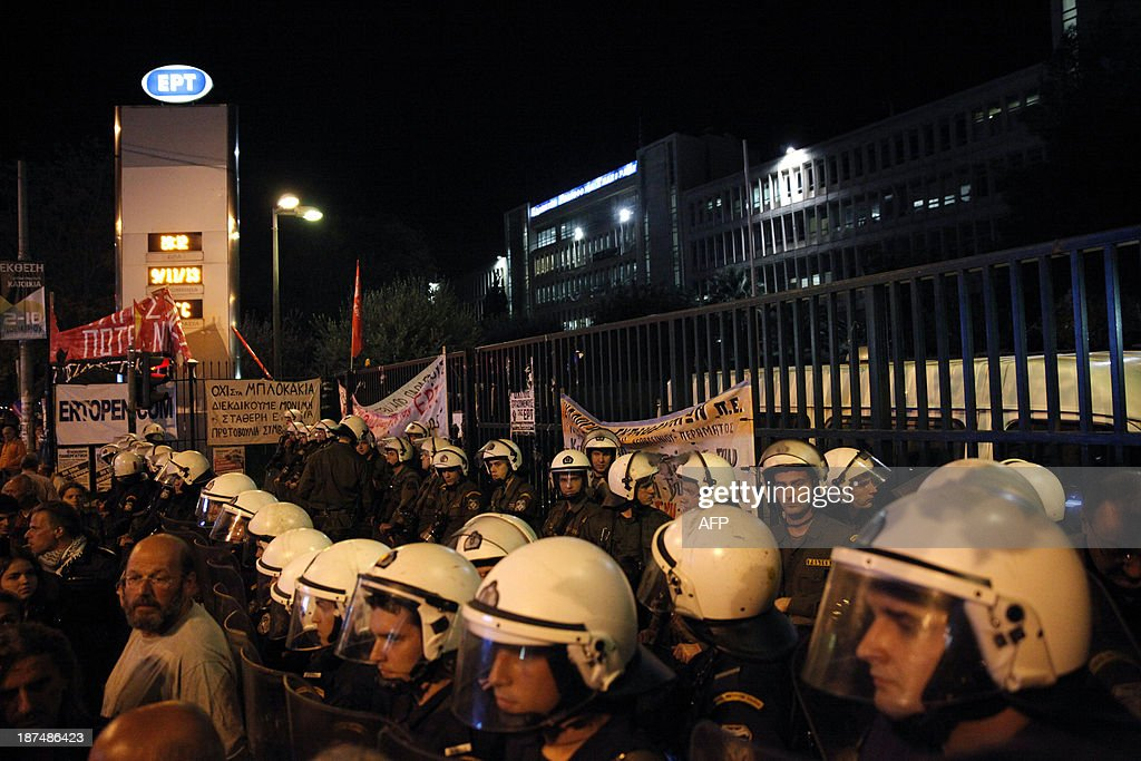 Riots police block the entrance of the former ERT headquarters during a demostration in Athens, on November 9, 2013. Greek riot police burst into the former ERT headquarters early on November 7 and forcibly removed employees who were occupying the site since its shock shutdown five months ago. AFP PHOTO / Kostis Ntantamis