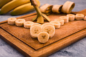 Ripe banana, cut into round slices, wooden background.