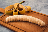 Ripe banana, white middle cut into transverse slices, wooden background, cut peel beautifully laid on the Board.