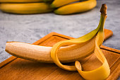 Ripe banana with cut yellow peel on wooden background.