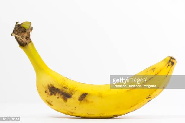 Ripe banana with stains on white background