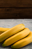 Ripe bananas in yellow peel on wooden background, vertical, copy space.