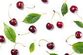 Fresh ripe cherry berries and cherry leaves pattern isolated on white background, top view