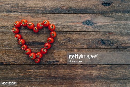 Ripe cherry tomatoes arranged in heart shape on wooden table : Stock Photo