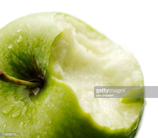 ripe crisp juicy green apple with chunk missing against white