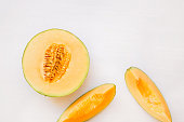 Ripe melon half and  slices on white background, top view, blank space