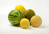 various types of melon on white wooden background