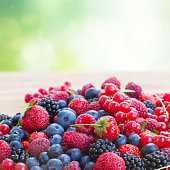 ripe of  berries on wooden table in garden  - blackberry, raspberry , red currant and blueberry