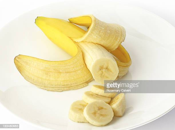 Ripe, organic banana peeled and partly sliced.
