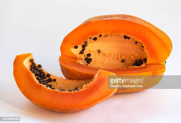 Ripe papaya fruit cut into two pieces on white background The fruit is dark orange in color with black seeds