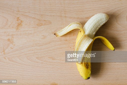 ripe peel banana on wooden cutting board top view : ストックフォト