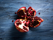 Ripe pomegranate on blue background cutout