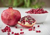 Ripe pomegranate seeds on a white wooden table. Fruit diet. Healthy lifestyle.Ripe pomegranate seeds on a white wooden table. Fruit diet. Healthy lifestyle.