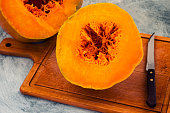Ripe pumpkin with an orange middle, cut into two parts, a knife on a wooden Board.