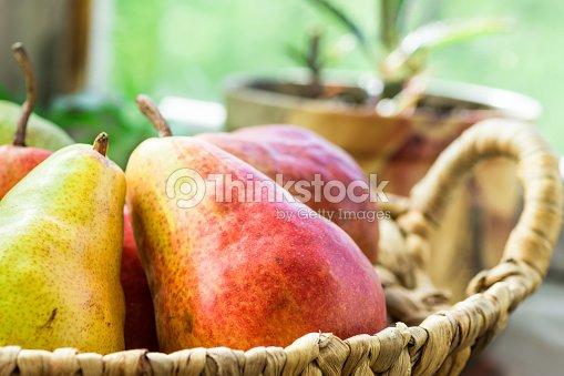 Peras org nicas rojo maduras en cesta de mimbre sobre la for Maduras en la cocina