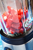 peeled ripe strawberries in a blender on a blue wooden table