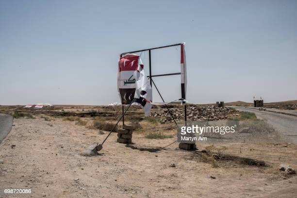 A ripped Iraqi national flag billboard June 20 2017 on the IraqSyria border in Nineveh Iraq The Popular Mobilisation Front forces composed of...
