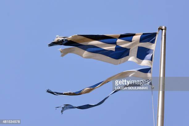 A ripped off Greek national flag flutters in central Athens on July 22 2015 Prime Minister Alexis Tsipras faces a new test of his authority in...