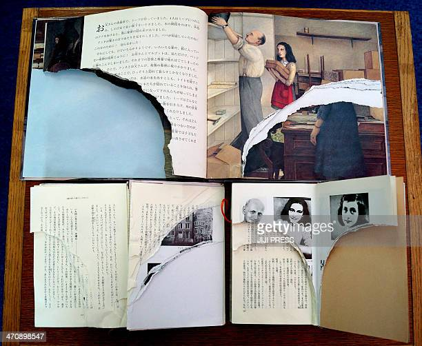 Ripped pages of three books of Anne Frank's 'Diary of Young Girl' are displayed at a library in Tokyo on February 21 2014 Scores of copies of Anne...