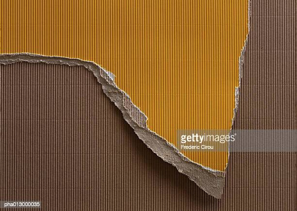 Ripped piece of yellow corrugated paper, on top of brown corrugated paper, close-up, full frame.