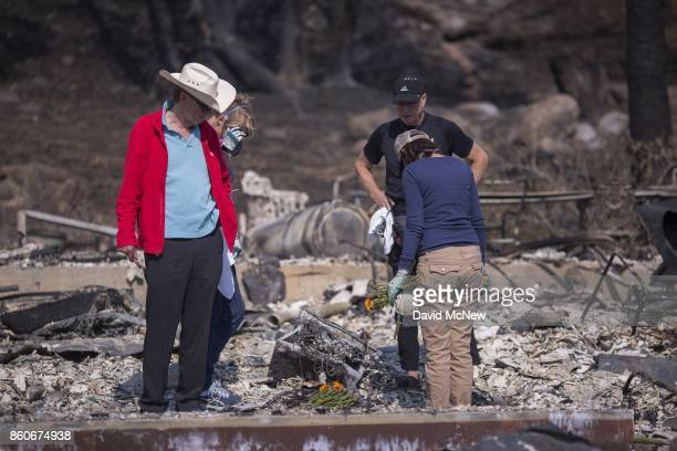 Rippey family sons Mike and Chuck and daughters Mimi and Liz say a prayer over the spot where their father died in the ruins of the house of...