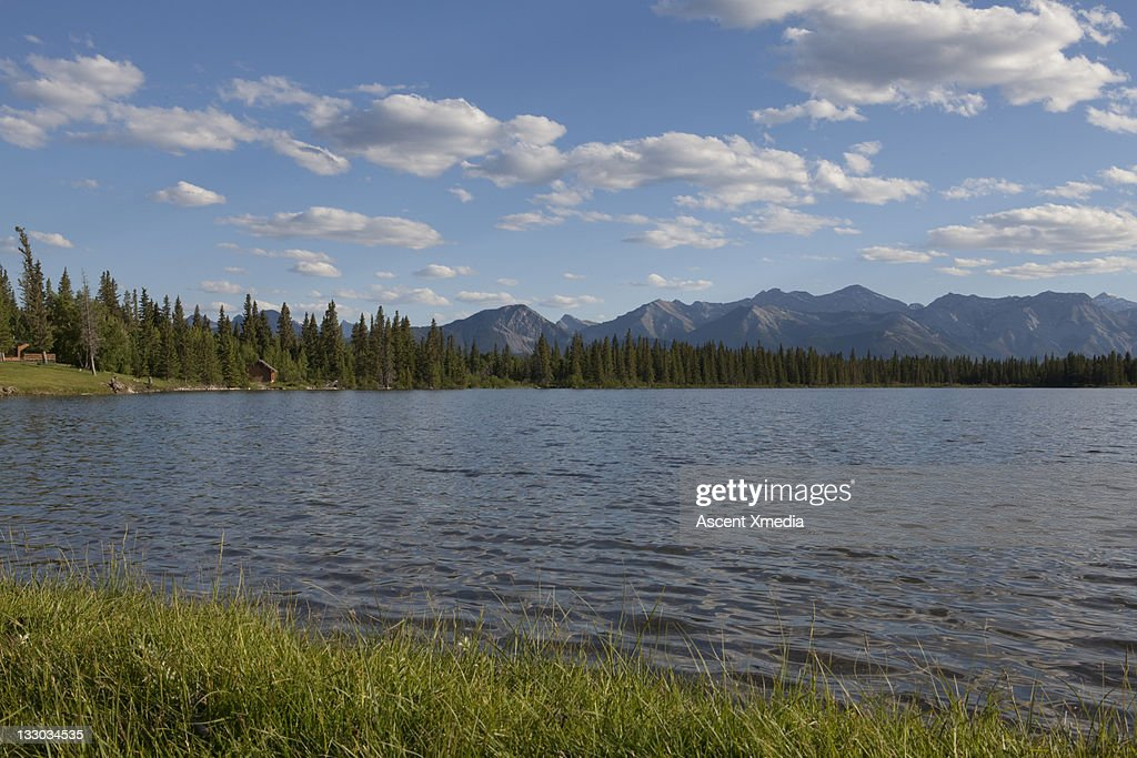 Ripples move across mountain lake, cabins distant : Stock Photo