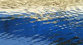 Reflections of a boat on the Gippsland Lakes in Australia form abstract ripples of blue and gold in the water.