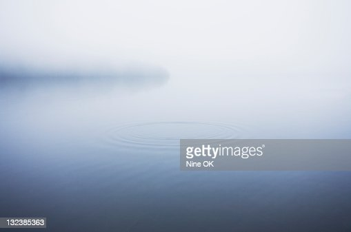 Ripples on surface of misty lake : Stock Photo