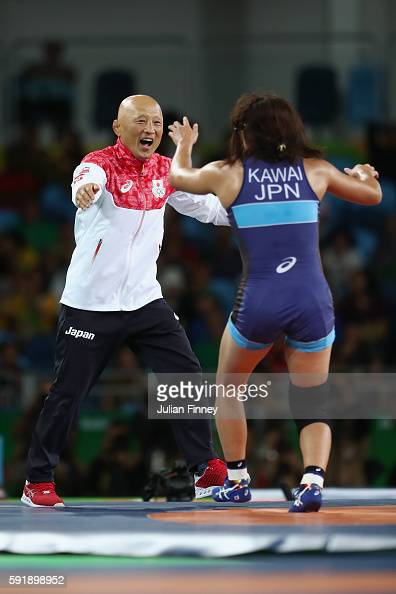 Risako Kawai of Japan celebrates with her coach Kazuhito Sakae after defeating Maryia Mamashuk of Belarus during the Women's Freestyle 63 kg Gold...