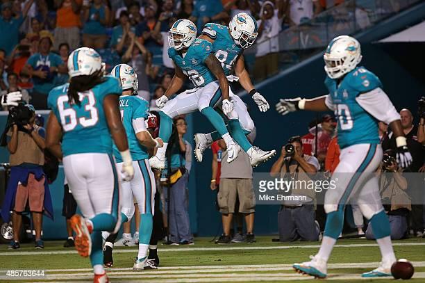 Rishard Matthews and Jordan Cameron of the Miami Dolphins celebrate a touchdown during a preseason game against the Atlanta Falcons at Sun Life...