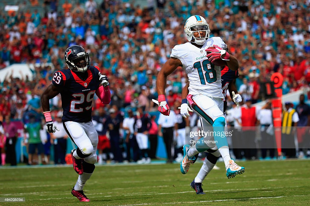 Rishard Matthews #18 of the Miami Dolphins runs the ball back for a touchdown in the first quarter as Andre Hal #29 of the Houston Texans looks on during a game at Sun Life Stadium on October 25, 2015 in Miami Gardens, Florida.