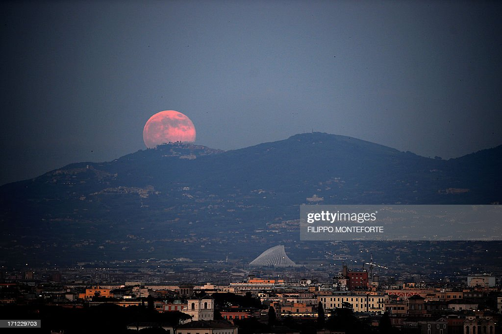 A rising moon is seen over the city of Rome on June 23, 2013. The full moon at perigee on called a 'supermoon' is the largest and closest full moon of the year as it appears 14 percent larger and 30 per cent brighter than normal as earth's satellite orbits within about 357,000 kilometers of our planet. AFP PHOTO / Filippo MONTEFORTE