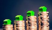 Kleine grüne Häuschen stehen auf Stapeln aus Münzen.