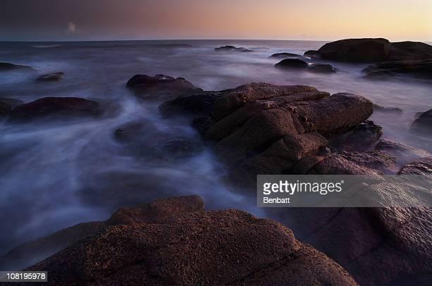 Maré crescente em Rocky litoral ao pôr do sol