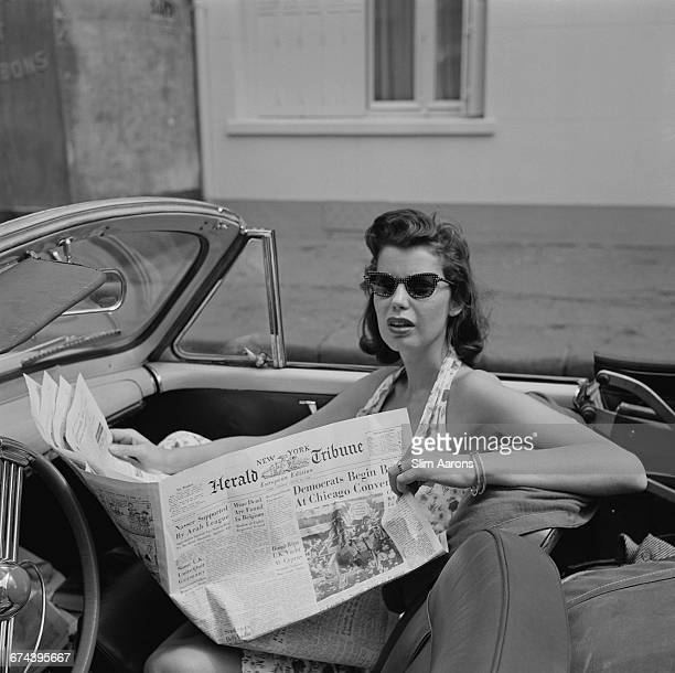 Rita Aarons wife of photographer Slim Aarons reading a New York Herald Tribune newspaper in Monaco 1956