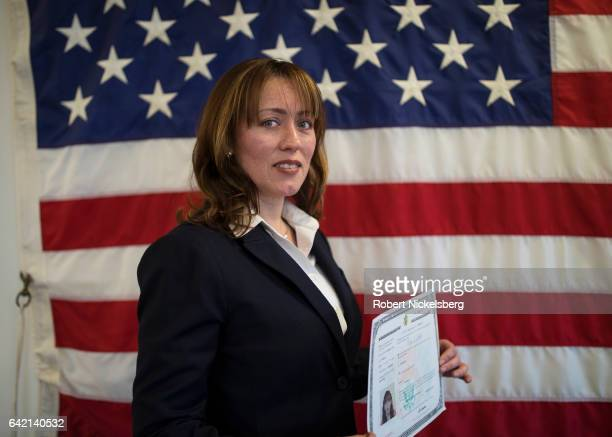 Rita Alejandra Alderete originally from Argentina stands for a picture holding her Certificate of Naturalization during a ceremony for new US...