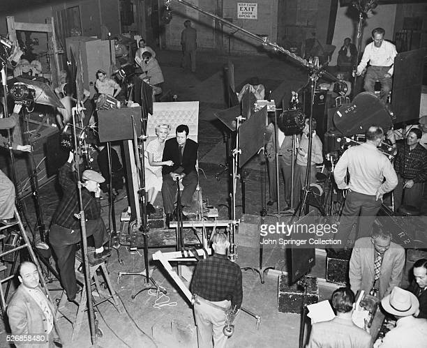 Rita Hayworth and Orson Welles sit waiting among a myriad of cameras lights and film crew members during a scene shoot for the film The Lady from...