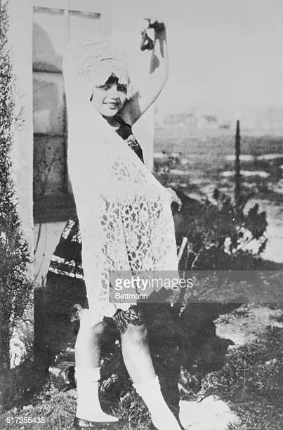 Rita Hayworth as child of ten with Spanish shawl and castanets in yard of her family's home