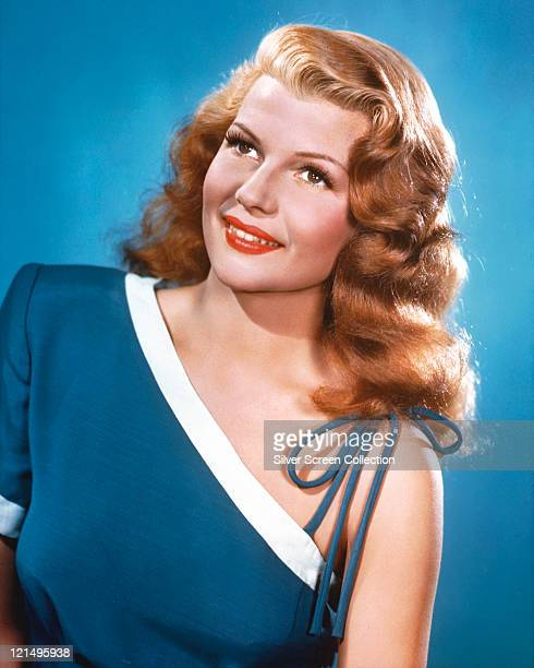 Rita Hayworth US actress and dancer wearing a blue offtheshoulder top with white trim in a studio portrait against a blue background circa 1945