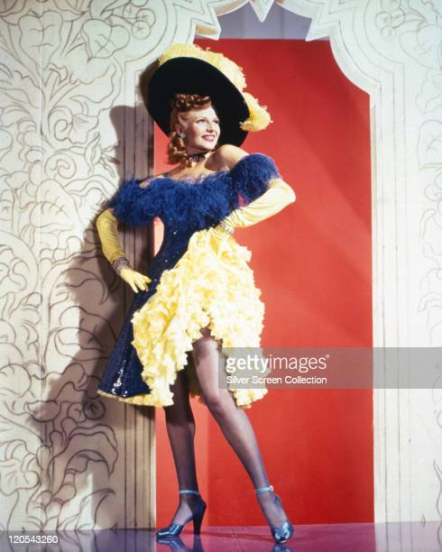 Rita Hayworth US actress and dancer wearing a blueandyellow musical hall outfit with a widebrimmed hat adorned with yellow ostrich feathers in a...